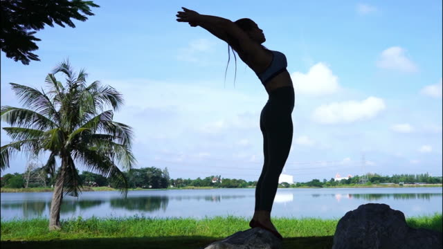 silhouette of asian sexy woman workout yoga and pilates , sunset and sunrise sky ,  zoom out - muscular contraction stock videos and b-roll footage