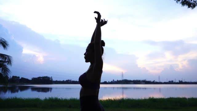 アジアのセクシーな女性ワークアウト ヨガとピラティス、日の出や日没の空のシルエット - 体を伸ばす点の映像素材/bロール
