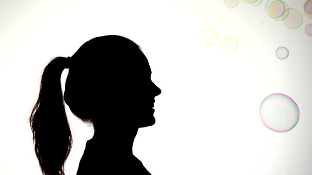 Silhouette of attractive woman popping a bubble