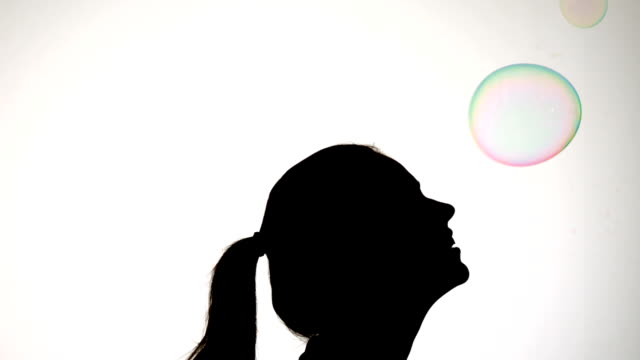 stockvideo's en b-roll-footage met silhouette of attractive woman popping a bubble with her nose - menselijke neus