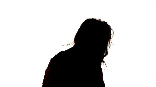 Silhouette of attractive woman shaking her hair