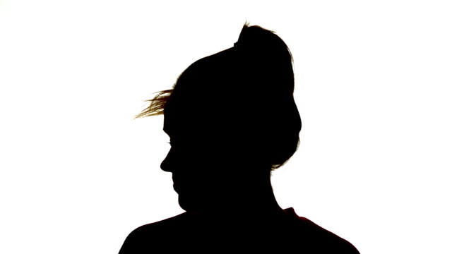 vidéos et rushes de silhouette of attractive woman shaking her ponytail - vignetage