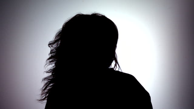 Silhouette of attractive woman tossing her hair