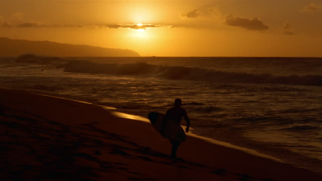 Silhouette of Australian surfer Nick Leslie carrying board across beach at sunset as waves break on shore / North Shore, Oahu, Hawaii