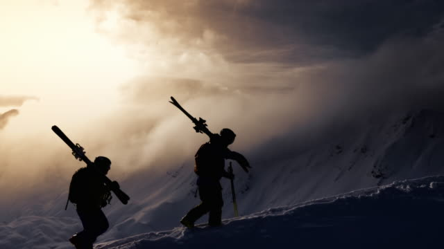 AERIAL Silhouette of backcountry skier walking up mountain ridge