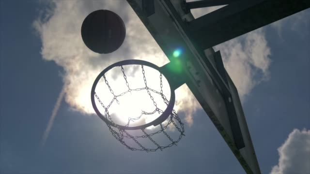 silhouette of basketball thrown into hoop with sky and sunshine background - basketballkorb stock-videos und b-roll-filmmaterial