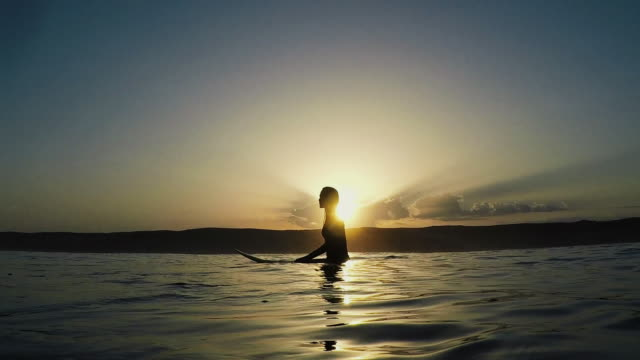 Silhouette of beautiful female surfer sitting on surfboard at sunrise in water at deserted sandy beach at Atlantic ocean coast in the south of France.