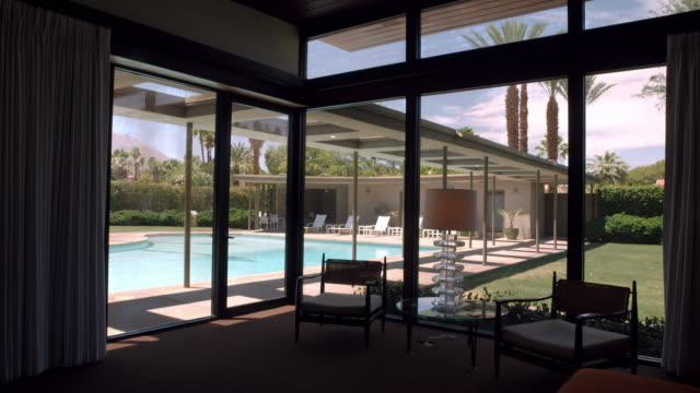 vídeos de stock, filmes e b-roll de ds silhouette of bedroom windows looking out towards swimming pool and pool house of mid-century modern home in the california desert - interior de casa modelo