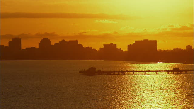 AERIAL Silhouette of Belmont Pier and downtown Long Beach backlit by setting sun, Long Beach, California, USA