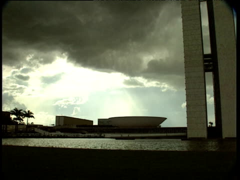 Silhouette of bird flies across brooding sky over National Congress of Brazil Brasilia