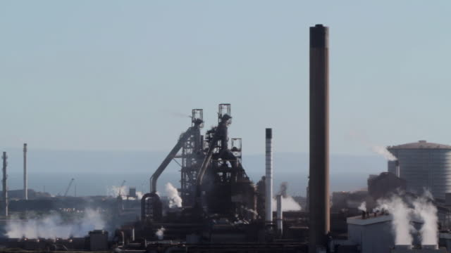 ws silhouette of blast furnaces and steam from high vantage point / port talbot, glamorgan, wales, uk - steel mill stock videos & royalty-free footage