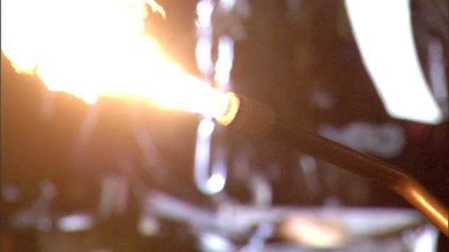 silhouette of blowtorch nozzle and spark lighter sticking in frame lighting torch flame in orange glow changing to blue glow torch moving out of... - steel worker stock videos & royalty-free footage