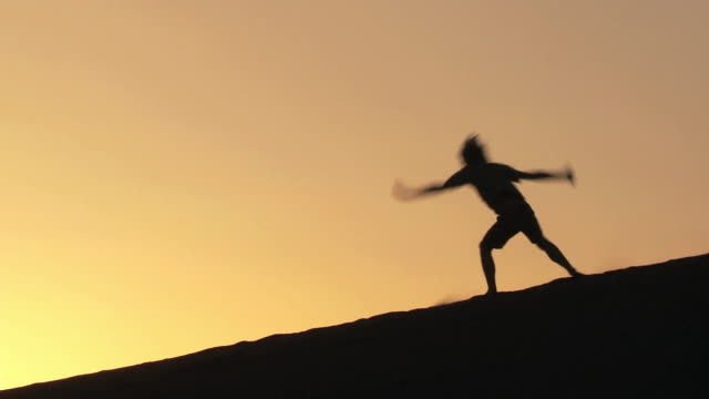 ws silhouette of boy cartwheeling down a sand dune against an orange sky / san pedro de atacama, norte grande, chile - sand dune stock videos and b-roll footage