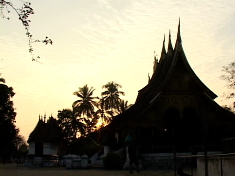 ws, silhouette of buddhist monastery at sunset, luang prabang, laos - turmspitze stock-videos und b-roll-filmmaterial