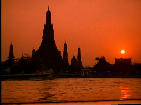 silhouette of buddhist temple (wat arun) with boats on chao phraya river in foreground at sunset / bangkok - romantische stimmung stock-videos und b-roll-filmmaterial