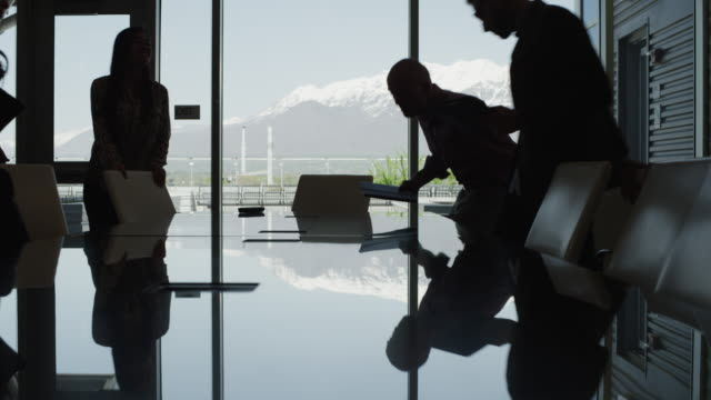 silhouette of business people sitting down in meeting / provo, utah, united states,  - controluce video stock e b–roll
