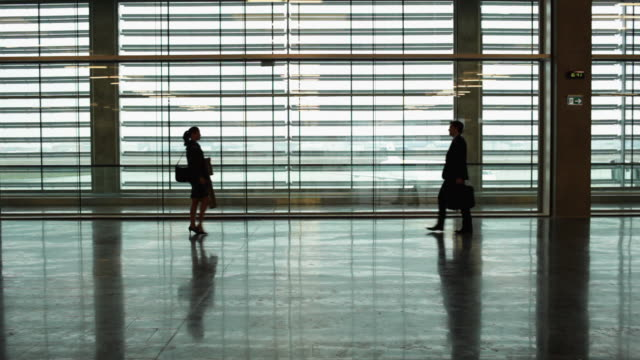 WS Silhouette of businessman and businesswoman meeting and shaking hands in airport terminal / Toulouse, Haute-Garonne, France
