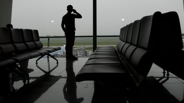 vídeos de stock, filmes e b-roll de silhueta de homem de negócios no aeroporto - portão
