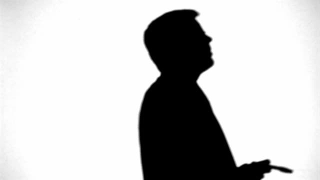 Silhouette of businessman pacing and smoking cigar