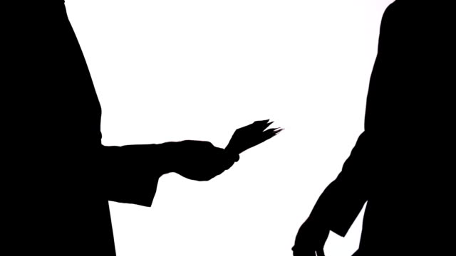 Silhouette of businessman passing a bribe