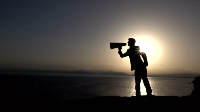 vídeos de stock e filmes b-roll de silhouette of businessman shouting through megaphone in sunset - perfil