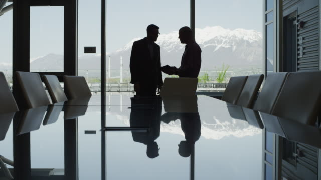 Silhouette of businessmen talking in conference room then walking away / Provo, Utah, United States,