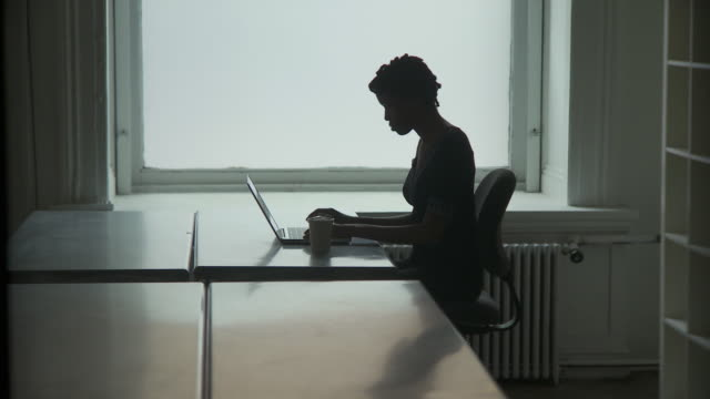 ws silhouette of businesswoman typing on laptop in office / new york city, new york, usa - silhouette stock videos & royalty-free footage