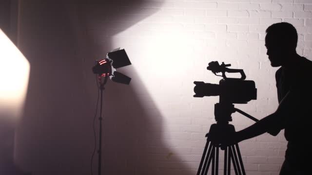 vídeos de stock, filmes e b-roll de silhouette of camera operator working on studio - set de filme