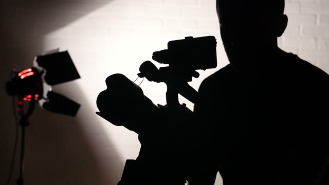 silhouette of camera operator working on studio - back lit stock videos & royalty-free footage