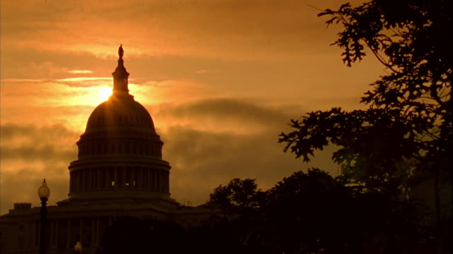 vídeos de stock e filmes b-roll de xws silhouette of capitol building trees w/ burnt orange yellow sky bg - capitol hill