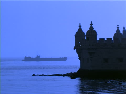 silhouette of cargo ship sailing on river with tower of belem in foreground / portugal / blue filter - cinematografi bildbanksvideor och videomaterial från bakom kulisserna