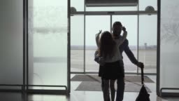 Silhouette of Caucasian young man entering the glass airport door with luggage. Little cheerful girl running up to her father. Arrival area, meeting after journey, tourism.