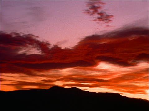 pan silhouette of clouds over dark landscape - romantische stimmung stock-videos und b-roll-filmmaterial