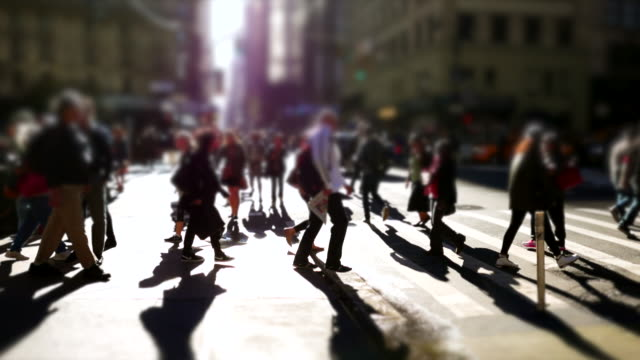 silhouette of commuters crossing street in the city. walking people background - 歩行者点の映像素材/bロール