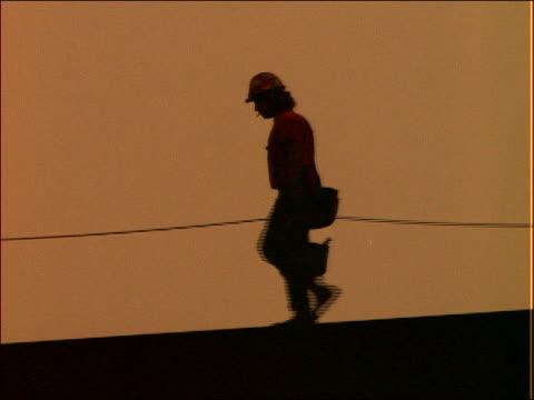 silhouette of construction worker walking on beam - solo uomini di età media video stock e b–roll