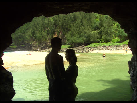 silhouette of couple in cave entrance, looking toward outside beach and water - see other clips from this shoot 1158 stock videos and b-roll footage