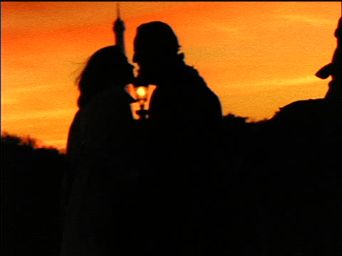 profile silhouette of couple kissing at sunset / eiffel tower in background / paris - 1998 stock-videos und b-roll-filmmaterial
