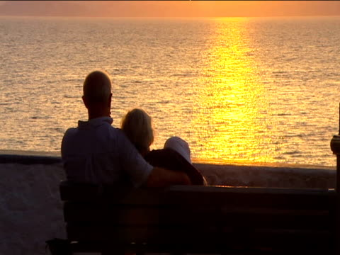 silhouette of couple sat on bench looking out to sunset reflecting on glistening sea - bench stock videos & royalty-free footage