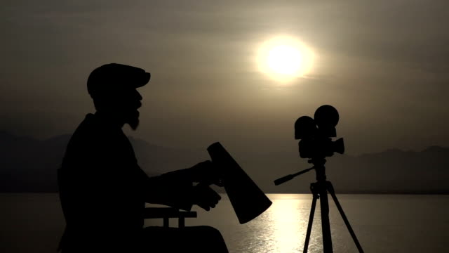 silhouette of director yelling trough a megaphone in sunset - film director stock videos & royalty-free footage