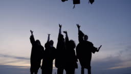 Silhouette of Diverse International Students Celebrating Graduation Tossing Caps in the air