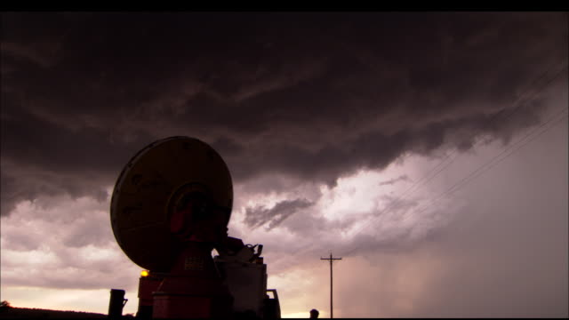 vídeos de stock, filmes e b-roll de ms, silhouette of doppler radar dish rotating against stormy sky, texas, usa - doppler