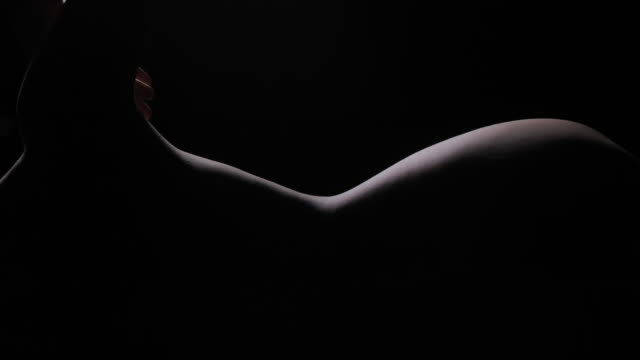 silhouette of elegant young woman erotic demonstrating her perfect sensual body in dark studio.portrait,body.real bodies - naked stock videos & royalty-free footage