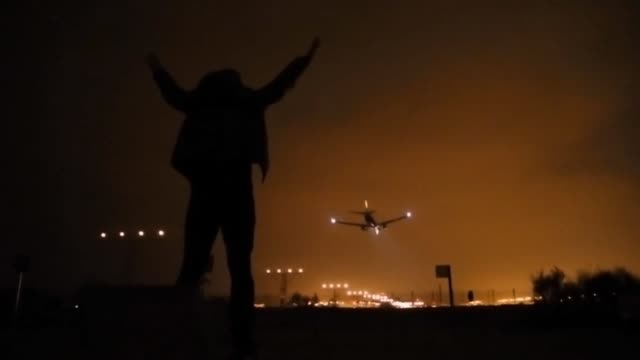 Silhouette of excited man contemplating the airplane landing in the Barcelona airport.