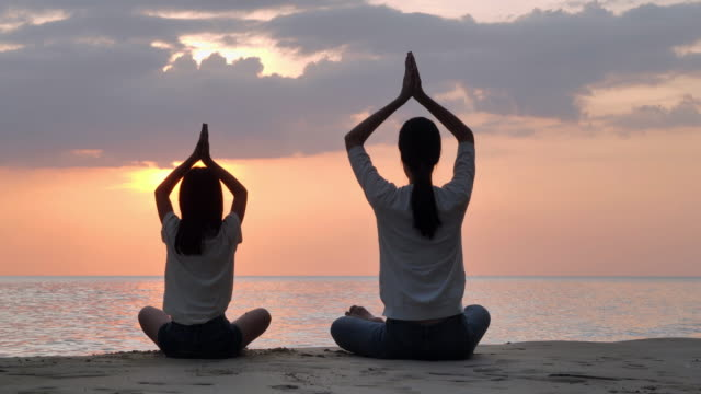 silhouette of family mother and child daughter are engaged in yoga on a beach in front of beautiful sea on sunset day.family,people,vacation,healthy,lifestyle,friendship.vacations - istock - daughter stock videos & royalty-free footage