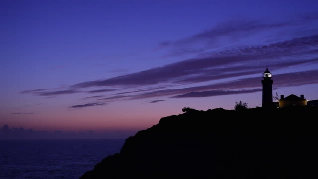 vídeos de stock e filmes b-roll de ws silhouette of farol de alfanzina lighthouse against sky at dusk / carvoeiro, algarve, portugal - purple