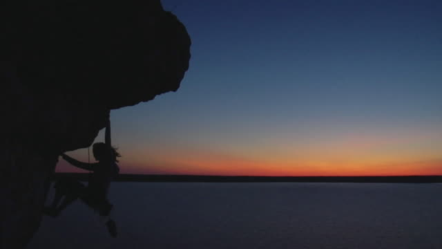WS Silhouette of female climber against sunset sky, Lion's Head, Ontario, Canada