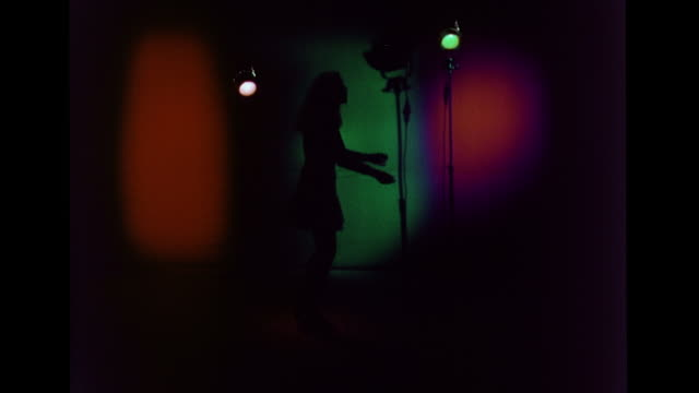 vídeos de stock, filmes e b-roll de silhouette of female dressed in skirt dancing inside darkened studio w/ red, green, magenta lighting patches on wall bg, same female silhouette... - 1960 1969
