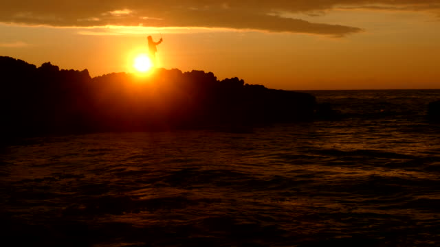 Silhouette of fisherman catching fish on sunset background
