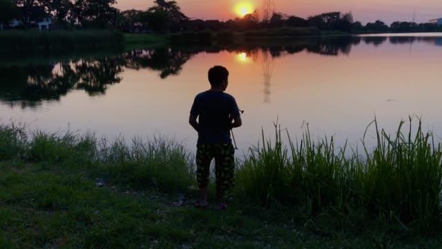 vídeos de stock, filmes e b-roll de silhueta de pescador pescaem em um rio com cena do nascer do sol - escapismo