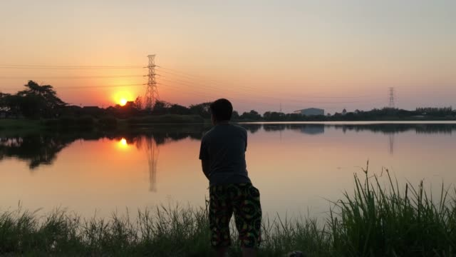 silhouette of  fisherman  fishing in a river with sunrise scene - catching stock videos & royalty-free footage